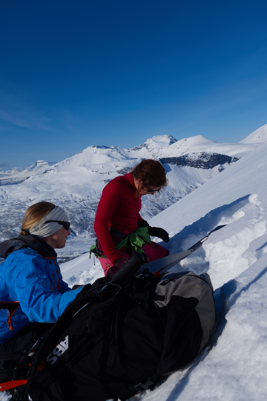 Kjersti and Linnea evaluating snow on Middagstinden in Lyngen.